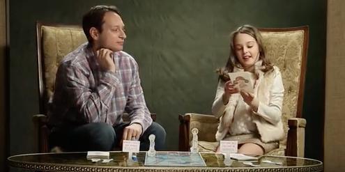 Video-Ausschnitt: Eine Tochter liest ihrem Vater eine Frage vor.