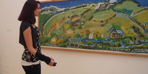 Museums-Besucherin mit Datenhandschuh, der Wege, Verweildauer und Herzfrequenz aufzeichnet.