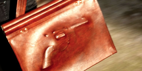 Wegen dieser Tasche mit dem Abdruck einer Pistole musste eine Frau eine Geldstrafe zahlen.