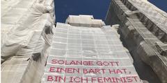 Staubschutzplane am Innsbrucker Dom mit feministischem Spruch.