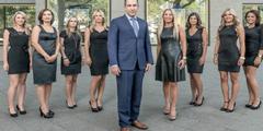 Altes Werbefoto: Der Chef steht vor seinen Mitarbeiterinnen, die enge und kurze Kleider tragen.