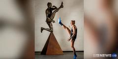 Footballerin Tayla Harris mit der Statue, die den Schuss zeigt, der Frauenhasser mobilisierte.